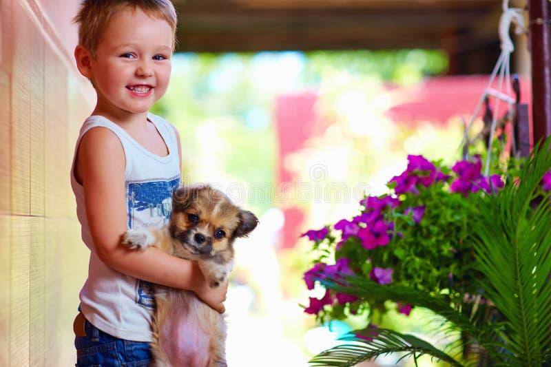 Νέο αγόρι που κρατά λίγο σκυλί κουταβιών στοκ φωτογραφία