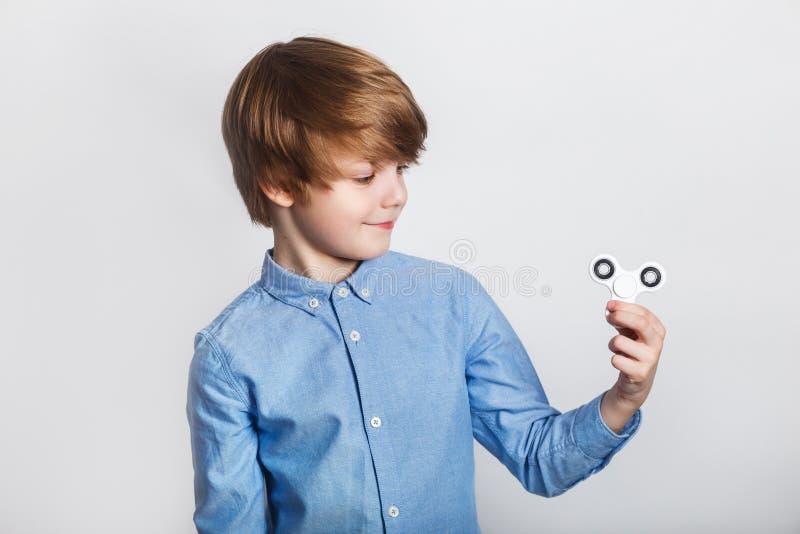 Νέο αγόρι που κρατά το δημοφιλές fidget παιχνίδι κλωστών - κλείστε επάνω το πορτρέτο Ευτυχές παιχνίδι παιδιών χαμόγελου με τον κλ στοκ εικόνες