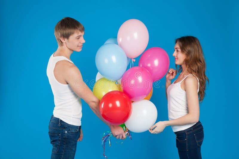Νέο αγόρι που παρουσιάζει baloons σε ένα κορίτσι στοκ εικόνα με δικαίωμα ελεύθερης χρήσης