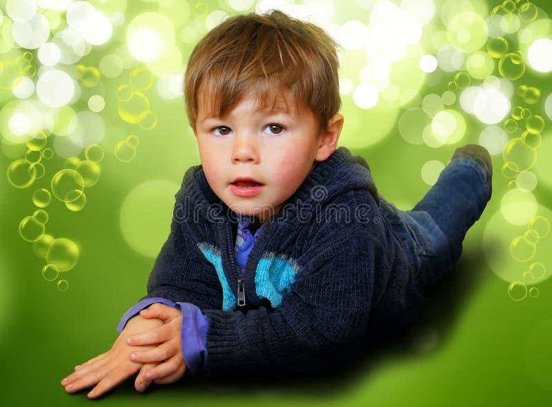 Νέο αγόρι που περιβάλλεται στις φυσαλίδες & bokeh στοκ εικόνα