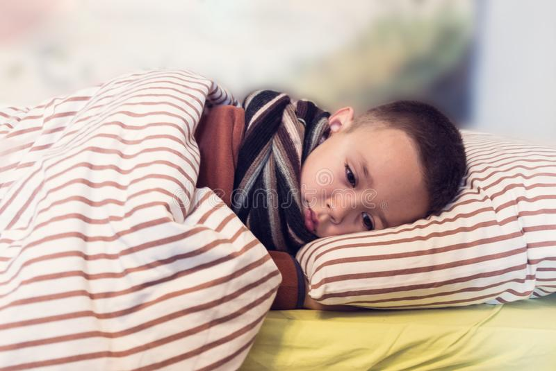 Νέο αγόρι που φορά το πουλόβερ και έναν ύπνο μαντίλι στο κρεβάτι του ενώ έχοντας γρίπη βασική επεξεργασία Γρίπη και εποχιακή έννο στοκ φωτογραφίες