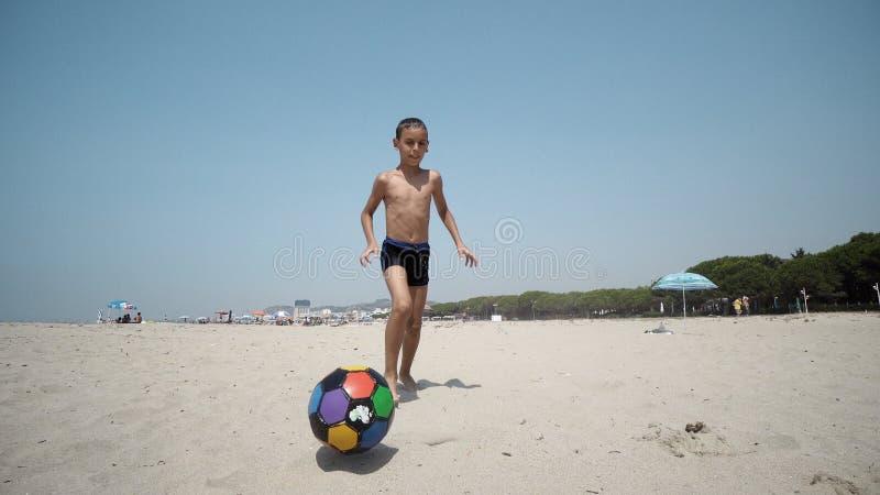 Νέο αγόρι στα παιχνίδια παραλιών με ένα ποδόσφαιρο στοκ εικόνες