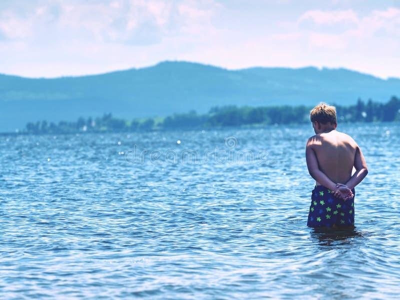 Νέο αγόρι στην μπλε παραμονή σορτς κολύμβησης στο κρύο νερό της λίμνης στοκ εικόνα