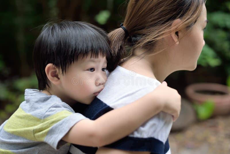 Νέο αγόρι στην πλάτη της μητέρας του: από την εστίαση στοκ εικόνες
