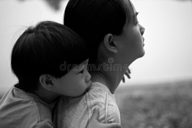 Νέο αγόρι στην πλάτη της μητέρας του: Μαλακή εστίαση στοκ εικόνα