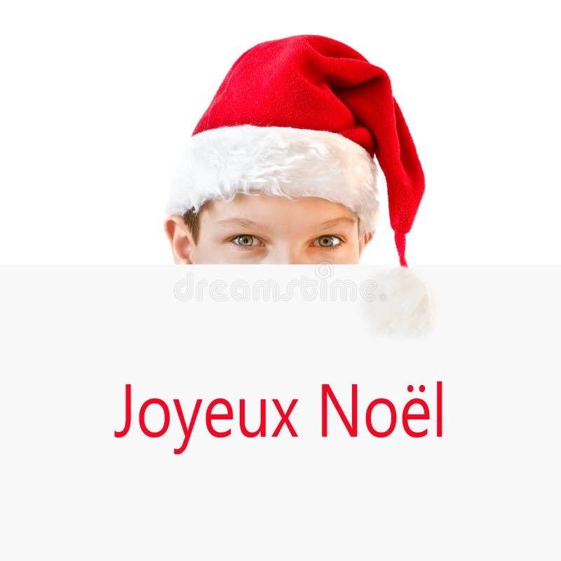 Νέο αγόρι στο κόκκινο κρύψιμο καπέλων Santa πίσω από ένα έγγραφο Joyeux Noel στοκ εικόνα