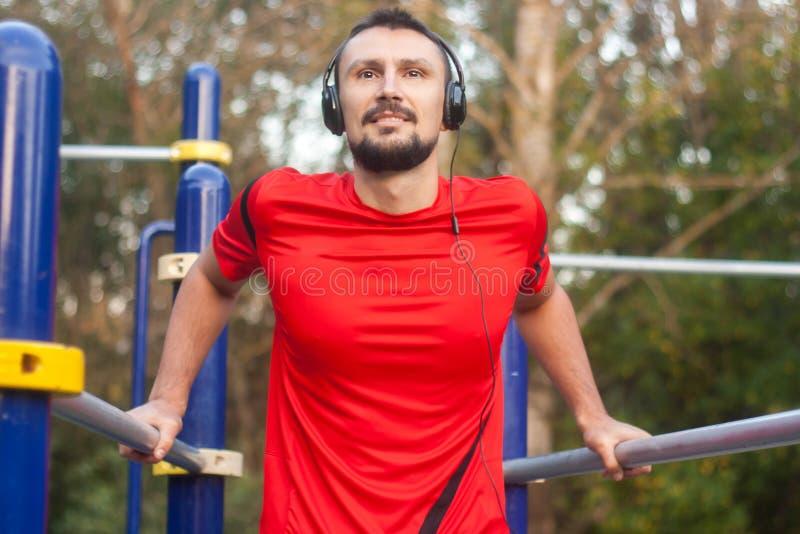 Νέο αθλητικό άτομο που κάνει τις αθλητικές ασκήσεις υπαίθρια στο πάρκο στοκ φωτογραφία