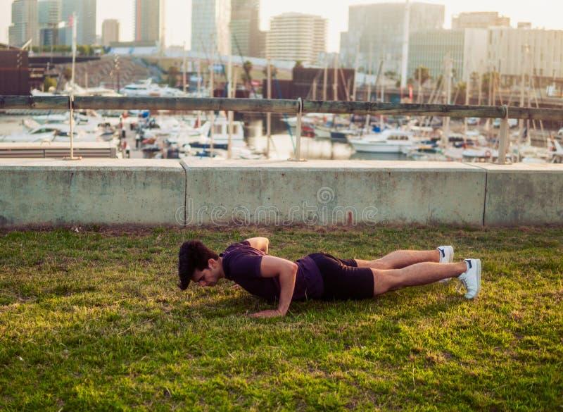 Νέο αθλητικό άτομο που κάνει pushups τις ασκήσεις στο πάρκο στοκ φωτογραφίες