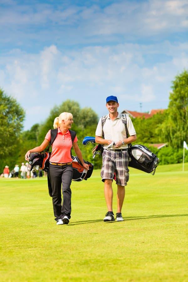 Νέο αθλητικό παίζοντας γκολφ ζευγών σε μια σειρά μαθημάτων στοκ φωτογραφίες με δικαίωμα ελεύθερης χρήσης