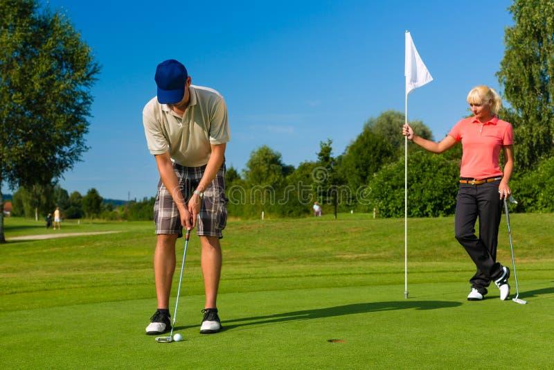 Νέο αθλητικό παίζοντας γκολφ ζευγών σε μια σειρά μαθημάτων στοκ εικόνες