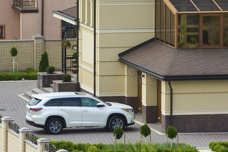 Νέο ακριβό άσπρο σπορ αυτοκίνητο Honda που σταθμεύουν μπροστά από την πόρτα γκαράζ στο στρωμένο well-kept ναυπηγείο με τον πράσιν στοκ εικόνα