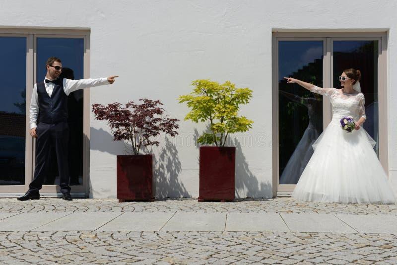 Νέο ακριβώς παντρεμένο ζευγάρι που δείχνει ο ένας στον άλλο στοκ εικόνες