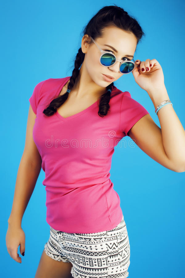Νέο αρκετά εφηβικό σύγχρονο κορίτσι hipster που θέτει το συναισθηματικό ευτυχές χαμόγελο στο μπλε υπόβαθρο, έννοια ανθρώπων τρόπο στοκ φωτογραφίες