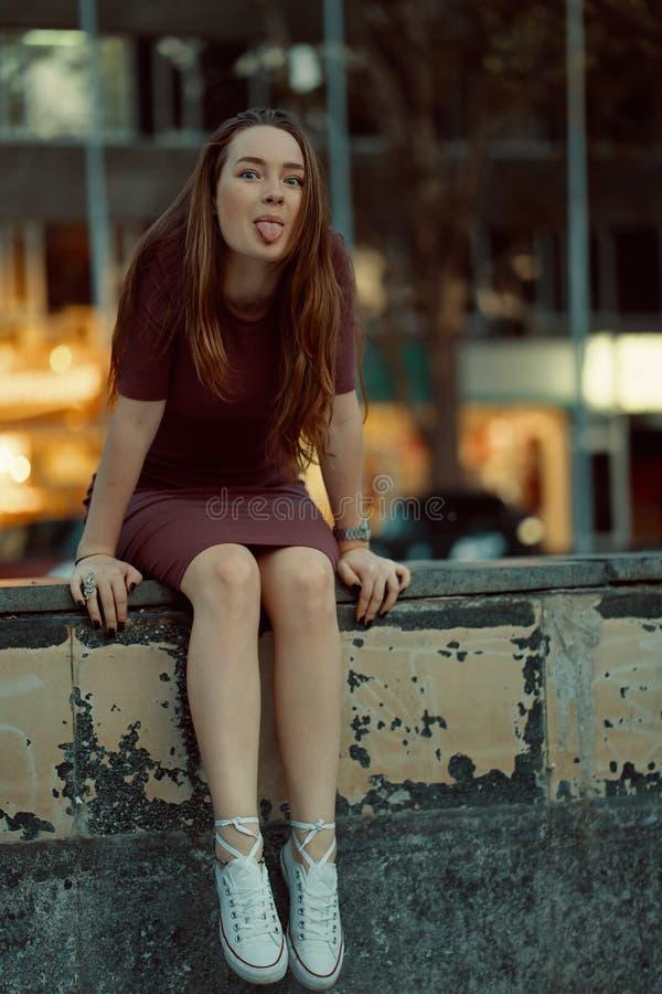 Νέο αρκετά κοκκινωπό ευτυχές χαμογελώντας κορίτσι που παρουσιάζει τη γλώσσα και havin στοκ εικόνα