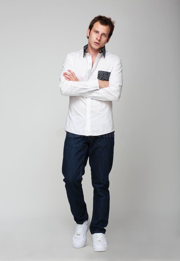 Νέο αρσενικό στα τζιν και τοποθέτηση πουκάμισων σε ένα στούντιο στοκ εικόνες με δικαίωμα ελεύθερης χρήσης