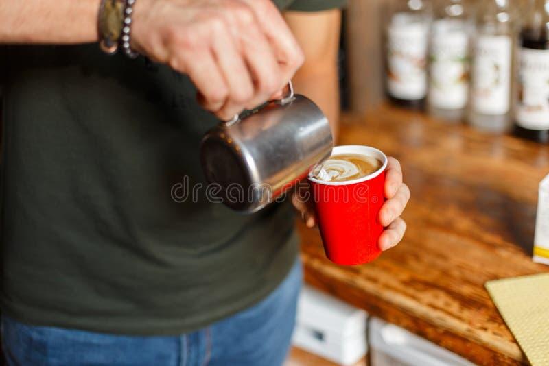 Νέο αρσενικό barista που κατασκευάζει latte τον καφέ στην εκλεκτής ποιότητας καφετερία Τα χέρια των ατόμων κρατούν ένα φλυτζάνι μ στοκ φωτογραφία με δικαίωμα ελεύθερης χρήσης