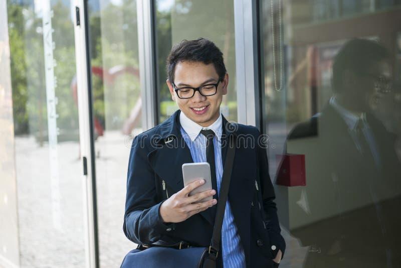 Νέο ασιατικό άτομο που εξετάζει το κινητό τηλέφωνο στοκ εικόνες