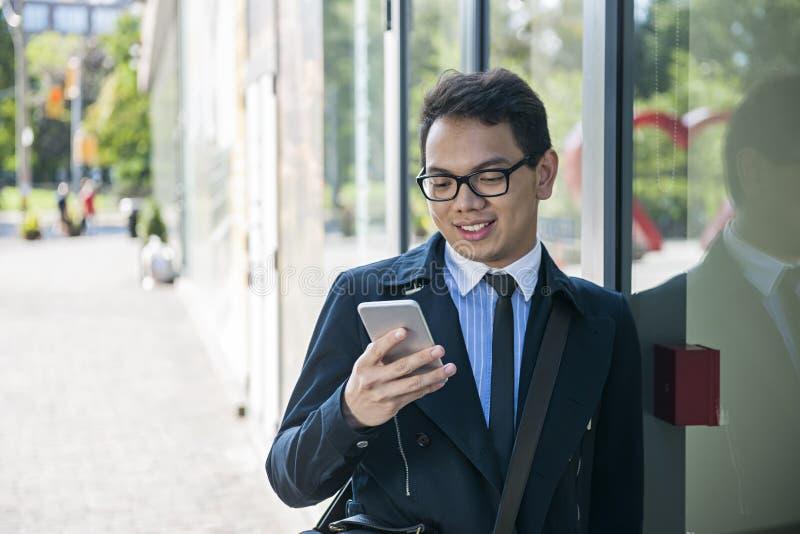 Νέο ασιατικό άτομο που εξετάζει το κινητό τηλέφωνο στοκ φωτογραφία με δικαίωμα ελεύθερης χρήσης