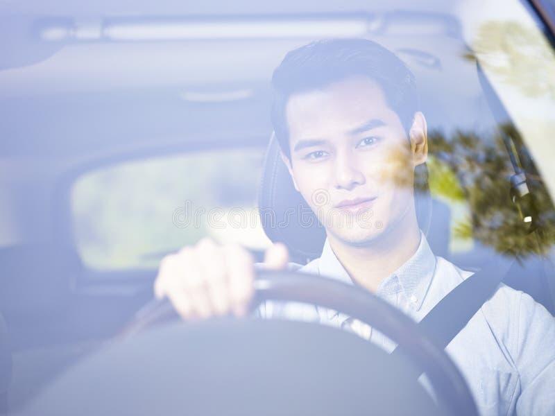 Νέο ασιατικό άτομο που οδηγεί ένα αυτοκίνητο στοκ εικόνες