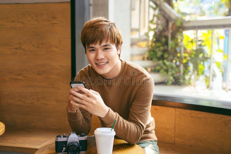 Νέο ασιατικό άτομο που χρησιμοποιεί το έξυπνο τηλέφωνο κατά τη διάρκεια της κατοχής του προγεύματος, coffe στοκ εικόνες