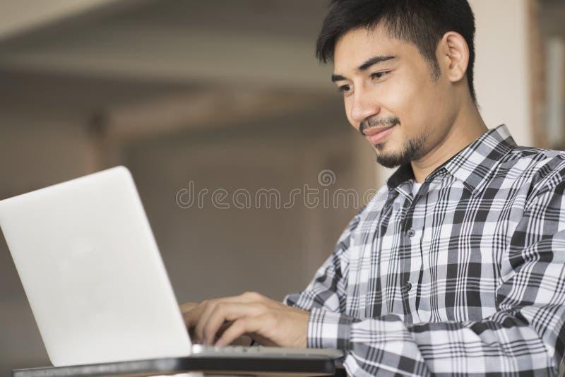 Νέο ασιατικό άτομο που χρησιμοποιεί το lap-top στο σπίτι στοκ εικόνα