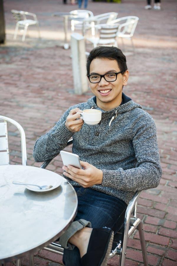 Νέο ασιατικό άτομο στον υπαίθριο καφέ στοκ εικόνες