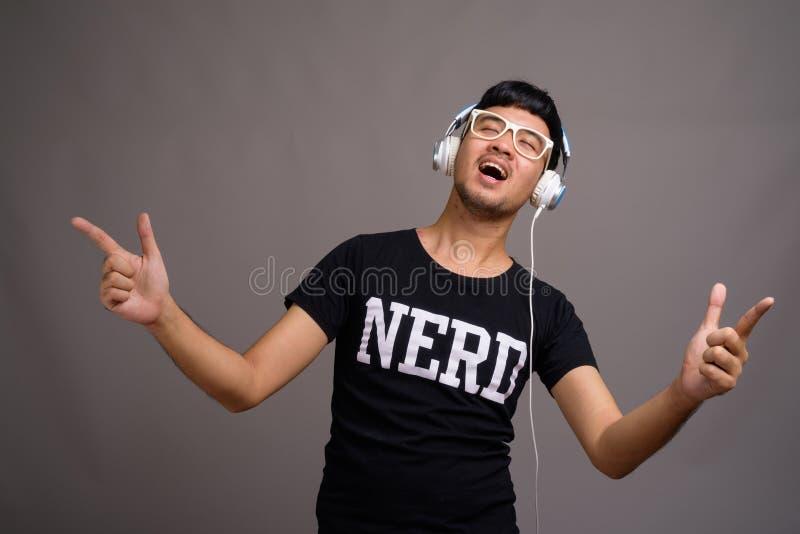 Νέο ασιατικό άτομο nerd που ακούει τη μουσική στο γκρίζο κλίμα στοκ φωτογραφία με δικαίωμα ελεύθερης χρήσης