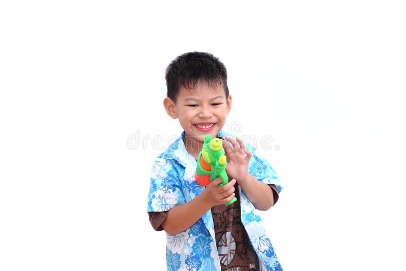 Νέο ασιατικό αγόρι με το πυροβόλο όπλο νερού στο άσπρο υπόβαθρο παιχνίδι παιδιών στοκ φωτογραφία