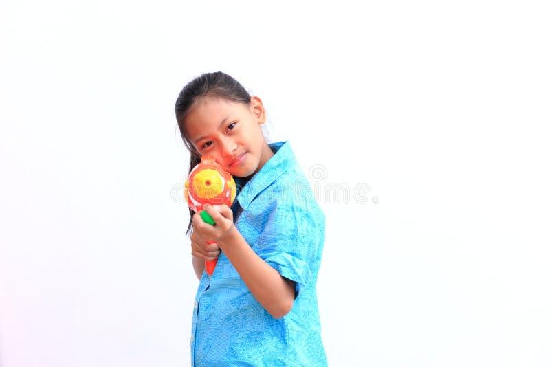 Νέο ασιατικό αγόρι με το πυροβόλο όπλο νερού στο άσπρο υπόβαθρο παιχνίδι παιδιών στοκ εικόνες