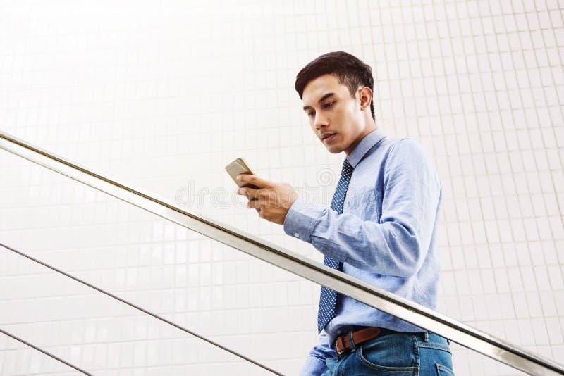 Νέο ασιατικό διαβασμένο επιχειρηματίας μήνυμα στο έξυπνο τηλέφωνο με σοβαρό στοκ εικόνες