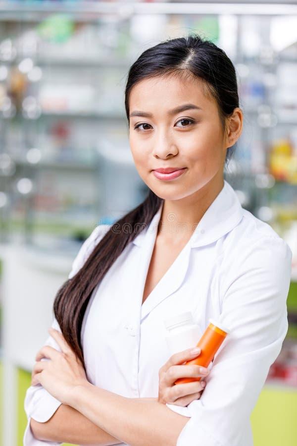 νέο ασιατικό εμπορευματοκιβώτιο εκμετάλλευσης φαρμακοποιών με το φάρμακο και χαμόγελο στη κάμερα στοκ εικόνες