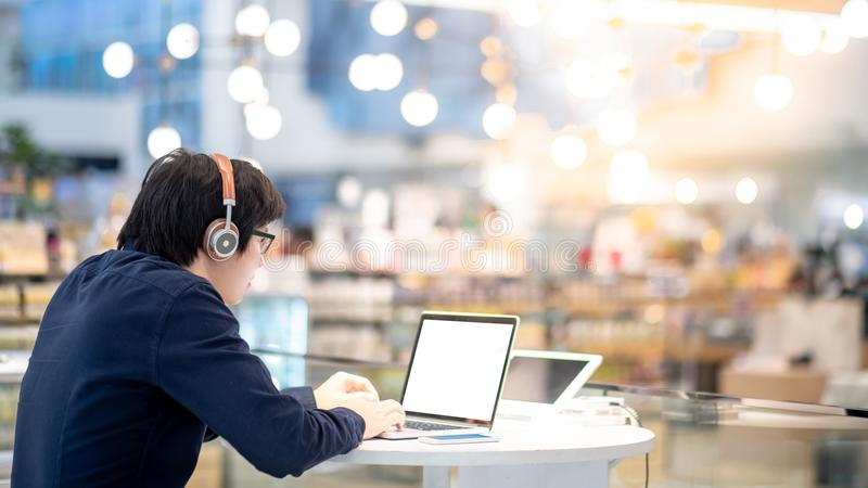 Νέο ασιατικό επιχειρησιακό άτομο που ακούει τη μουσική εργαζόμενο με το λ στοκ εικόνα