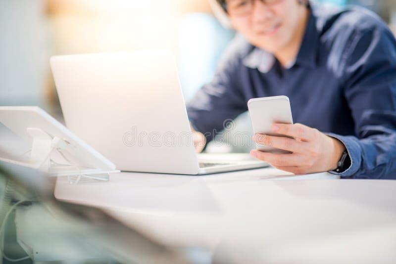 Νέο ασιατικό επιχειρησιακό άτομο που χρησιμοποιεί το smartphone εργαζόμενο με την περιτύλιξη στοκ φωτογραφία με δικαίωμα ελεύθερης χρήσης