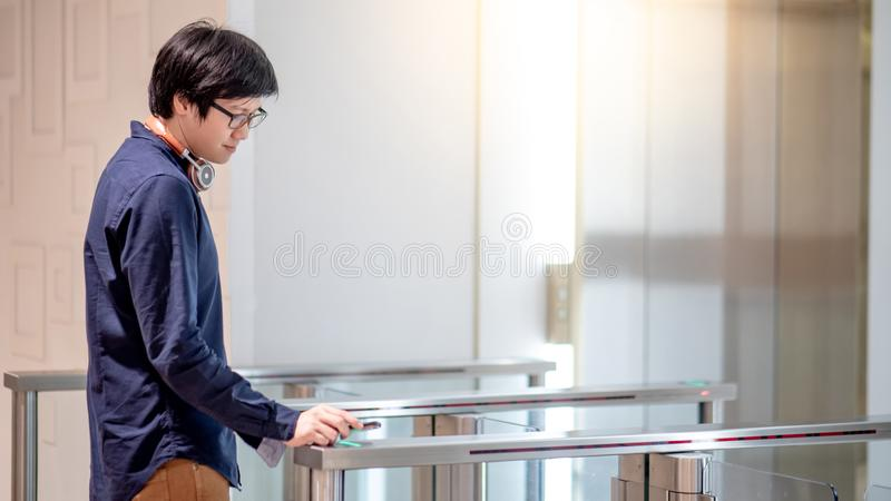 Νέο ασιατικό επιχειρησιακό άτομο που χρησιμοποιεί το smartphone στην ανοικτή αυτόματη πύλη στοκ εικόνες