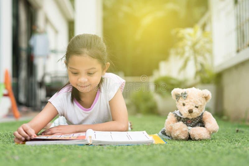 Νέο ασιατικό κορίτσι που διαβάζει ένα βιβλίο που βρίσκεται στο χορτοτάπητα σπιτιών της στοκ φωτογραφίες με δικαίωμα ελεύθερης χρήσης