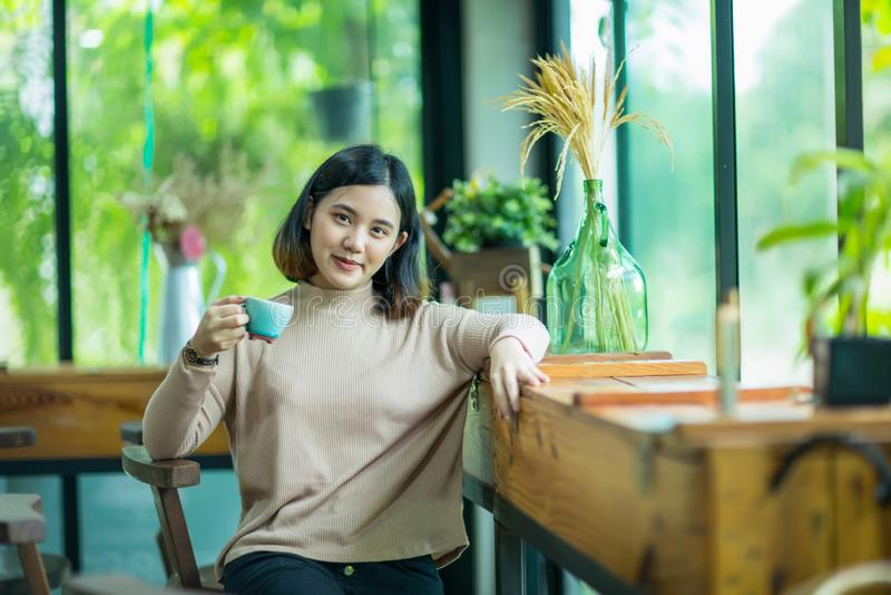 Νέο ασιατικό κορίτσι που κρατά ένα φλιτζάνι του καφέ στοκ εικόνα