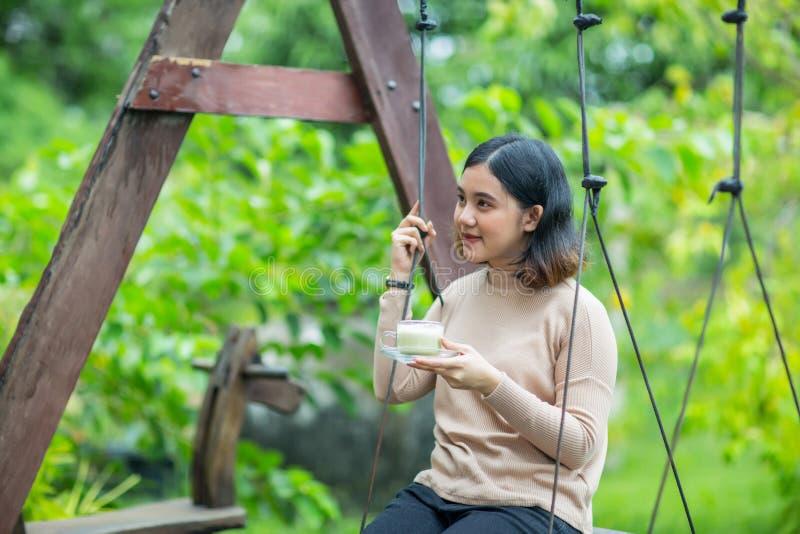 Νέο ασιατικό κορίτσι που κρατά ένα φλυτζάνι του πράσινου τσαγιού στην ξύλινη ταλάντευση στοκ φωτογραφία