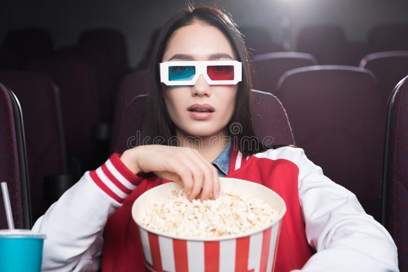 νέο ασιατικό κορίτσι στα τρισδιάστατα γυαλιά με το μεγάλο καλάθι popcorn του κινηματογράφου προσοχής στοκ εικόνες
