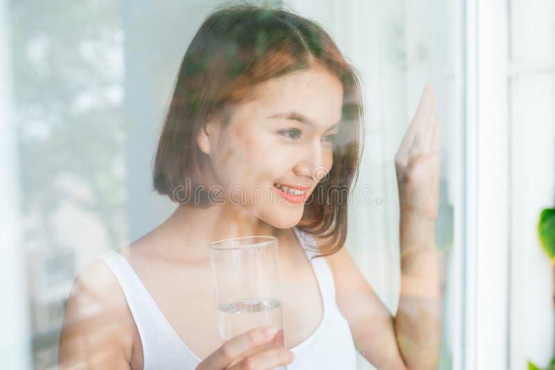 Νέο ασιατικό πόσιμο νερό γυναικών που κοιτάζει μέσω του παραθύρου στοκ φωτογραφίες με δικαίωμα ελεύθερης χρήσης