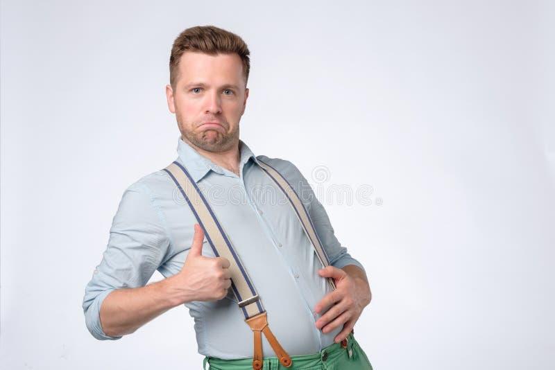 Νέο αστείο άτομο που παρουσιάζει αντίχειρα μετά από το νόστιμο γεύμα Συμπάθησε τα τρόφιμα στοκ εικόνες