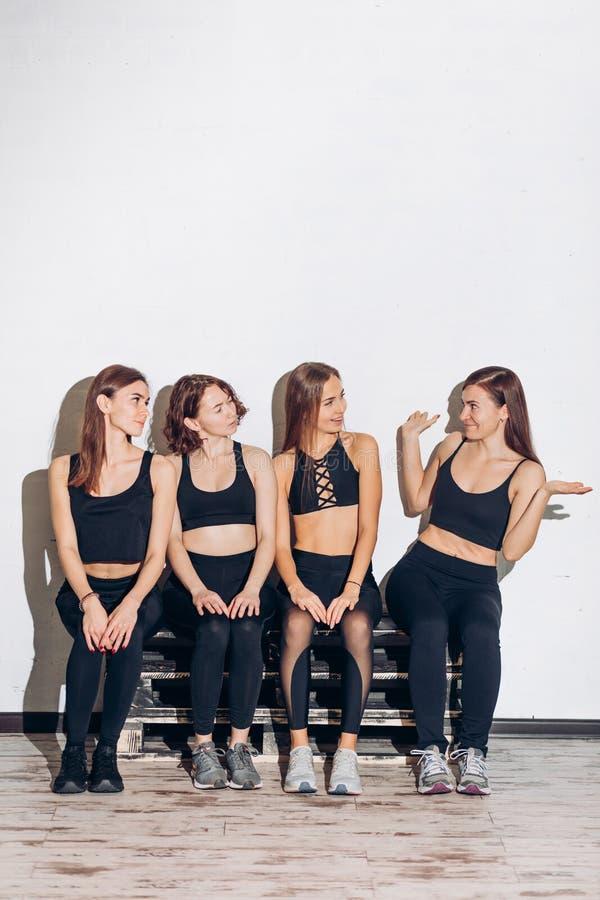 Νέο αστείο κορίτσι που παρουσιάζει τεχνάσματα στους φίλους της μετά από το workout στοκ εικόνα