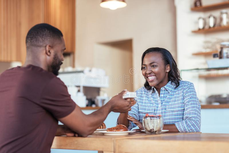 Νέο αφρικανικό άτομο που δίνει ένα παρόν στη χαμογελώντας φίλη του στοκ εικόνα με δικαίωμα ελεύθερης χρήσης
