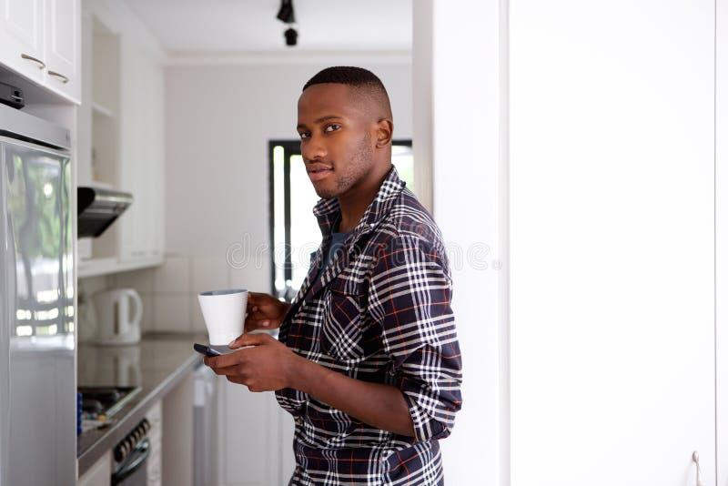 Νέο αφρικανικό άτομο στην κουζίνα με το κινητούς τηλέφωνο και τον καφέ στοκ εικόνες
