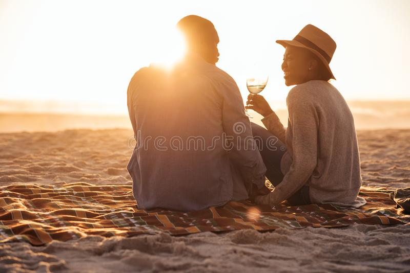 Νέο αφρικανικό ζεύγος που προσέχει ένα ηλιοβασίλεμα παραλιών και που πίνει το κρασί στοκ φωτογραφία με δικαίωμα ελεύθερης χρήσης