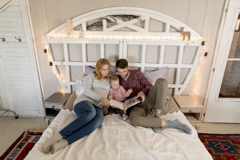Νέο βιβλίο ανάγνωσης γονέων στο χαριτωμένο μικρό κορίτσι στο κρεβάτι στοκ φωτογραφίες με δικαίωμα ελεύθερης χρήσης