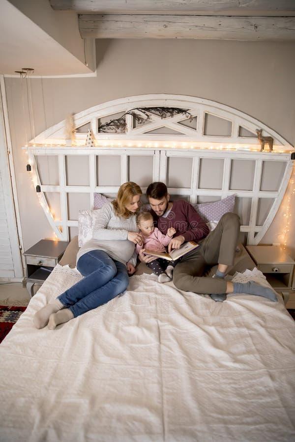 Νέο βιβλίο ανάγνωσης γονέων στο χαριτωμένο μικρό κορίτσι στο κρεβάτι στοκ εικόνα με δικαίωμα ελεύθερης χρήσης