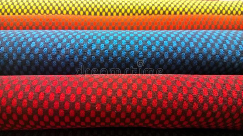 Νέο βιομηχανικό κίτρινο, πορτοκαλί, γκρίζο, μπλε και ιώδες υπόβαθρο ρόλων Έννοια: υλικό, ύφασμα, κατασκευή, εργοστάσιο ενδυμάτων, στοκ εικόνες