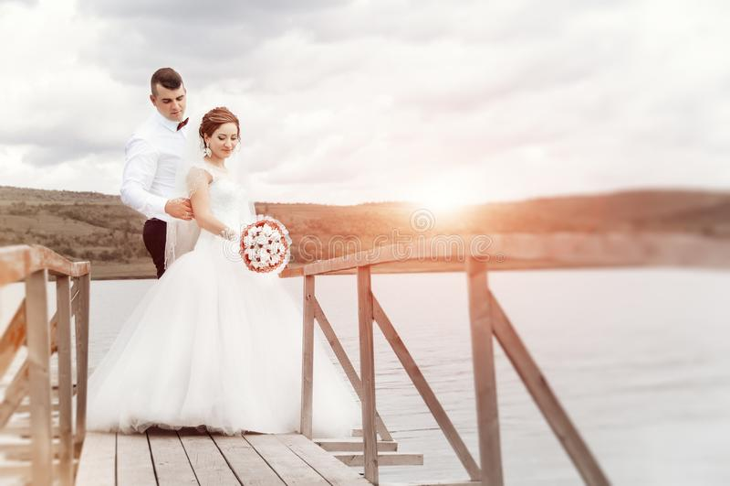 Νέο γαμήλιο ζεύγος που απολαμβάνει τις ρομαντικές στιγμές έξω δίπλα στο τ στοκ φωτογραφία