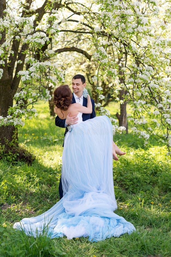 Νέο γαμήλιο ζεύγος που αγκαλιάζει στον ανθίζοντας κήπο άνοιξη Αγάπη και ρομαντικό θέμα στοκ εικόνες με δικαίωμα ελεύθερης χρήσης