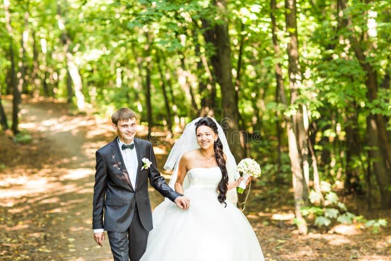 Νέο γαμήλιο ζεύγος που περπατά υπαίθρια στοκ φωτογραφία με δικαίωμα ελεύθερης χρήσης